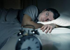 man looking at clock - sleeping condition
